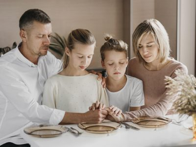 family-praying-while-holding-their-hands-together
